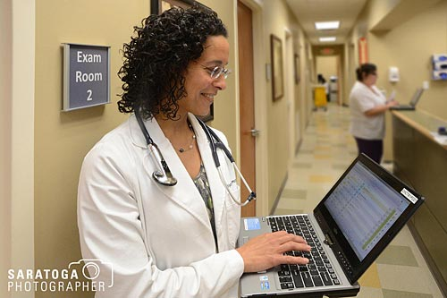 Doctor In Hallway Holding Laptop