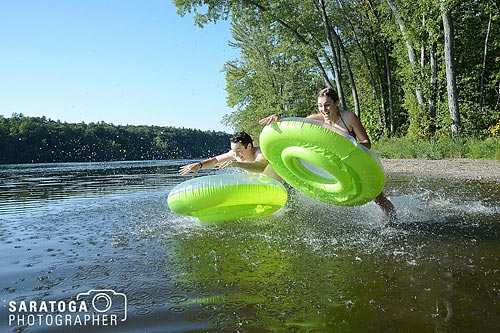 Two Kids With Innertubes Jumping Into Lake