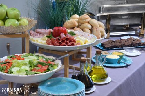 A buffet of food with a salad, meat plate and other items