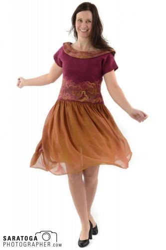 Full length view of standing model with gold skirt wearing handmade felted burgundy top on white background